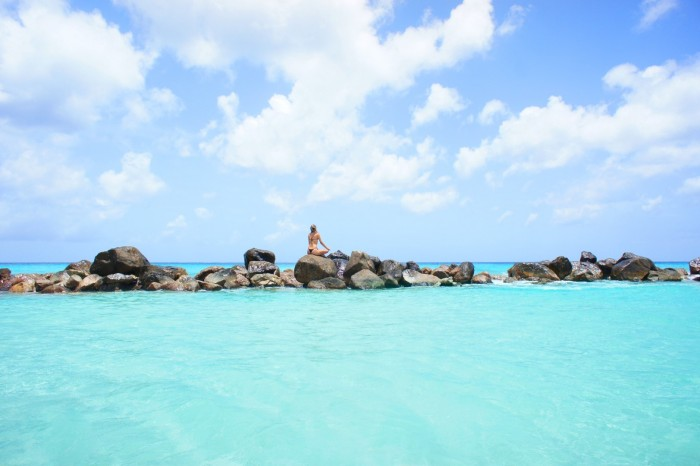 Garota pratica yoga nas rochas da praia - Credito ATA