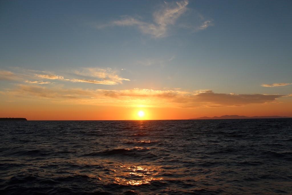 Pôr do sol visto do barco, momento imperdível em Santorini
